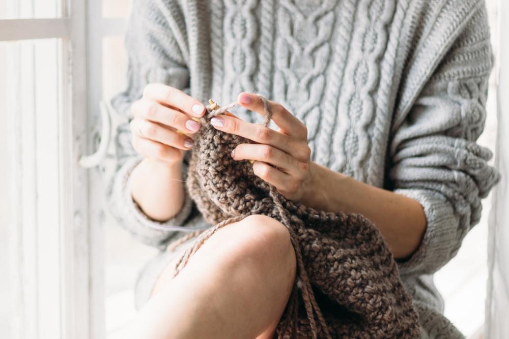 セーターを着てニットを編む女性