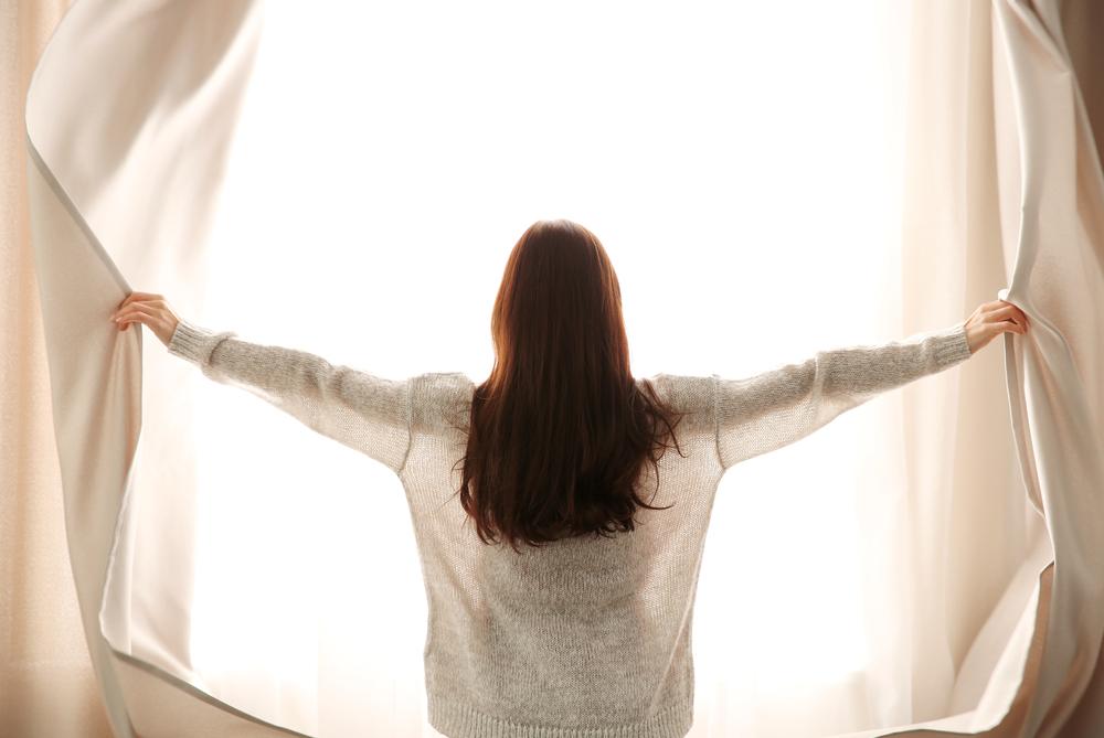カーテンを開ける女性の写真