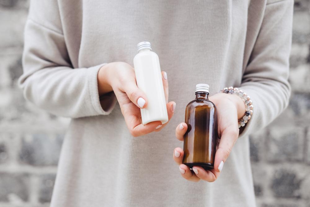 化粧水のボトルを手に持つ女性