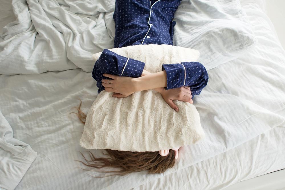 枕で顔を隠す女性