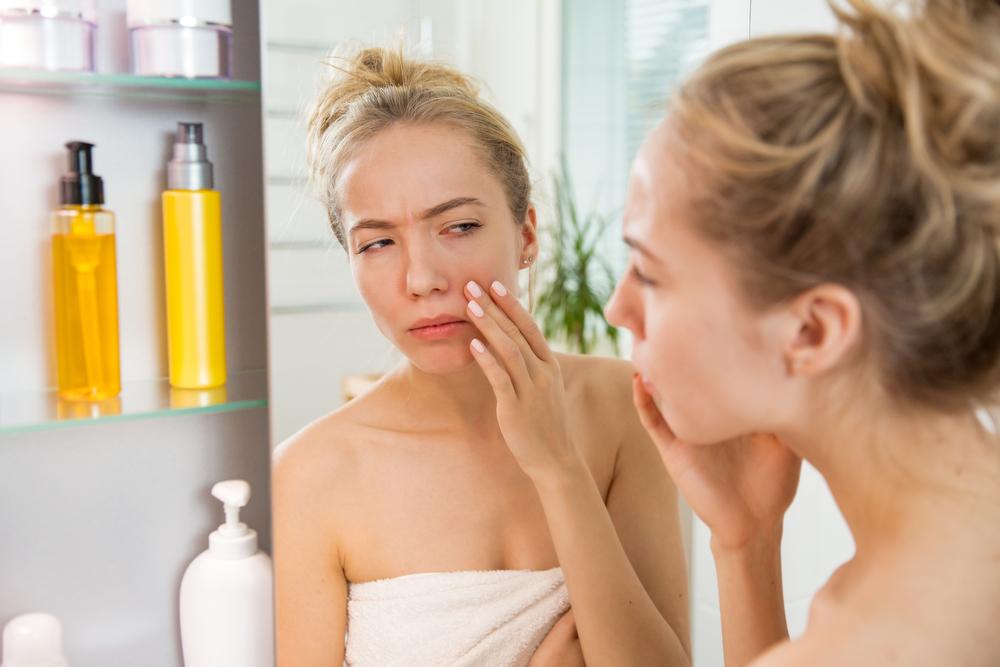 鏡で肌を見ている女性
