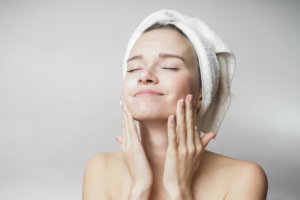 お風呂上がりに顔を触っている女性