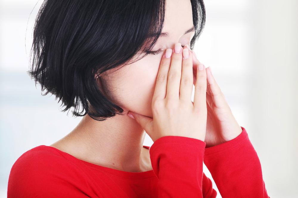 鼻を触っている女性