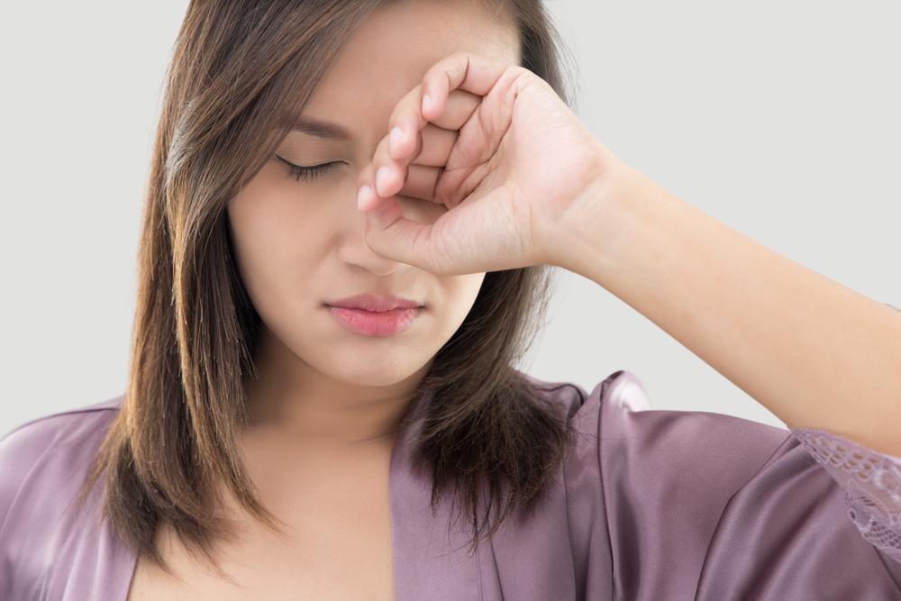目を擦っている女性