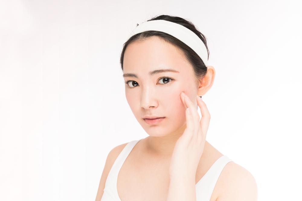 頬を触っている日本人女性