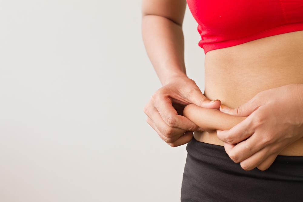 お腹の脂肪を摘まむ女性