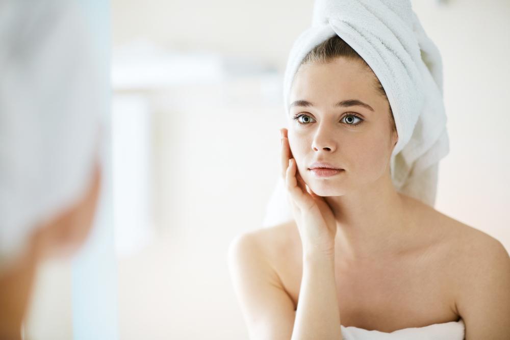 鏡で肌の状態をチェックする女性