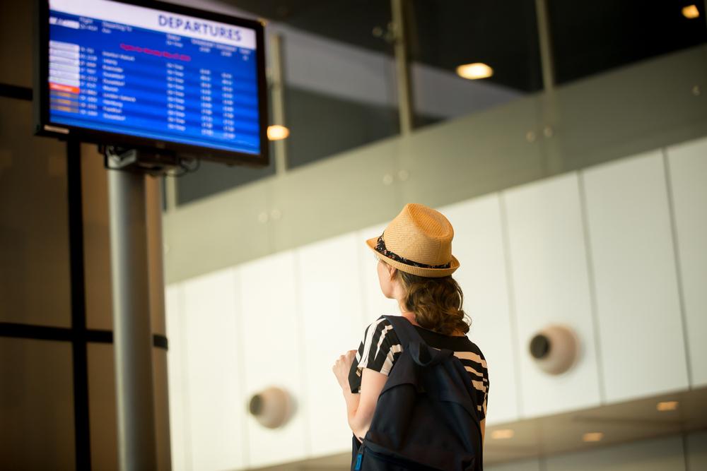 空港で自分のフライト時間をチェックする女性