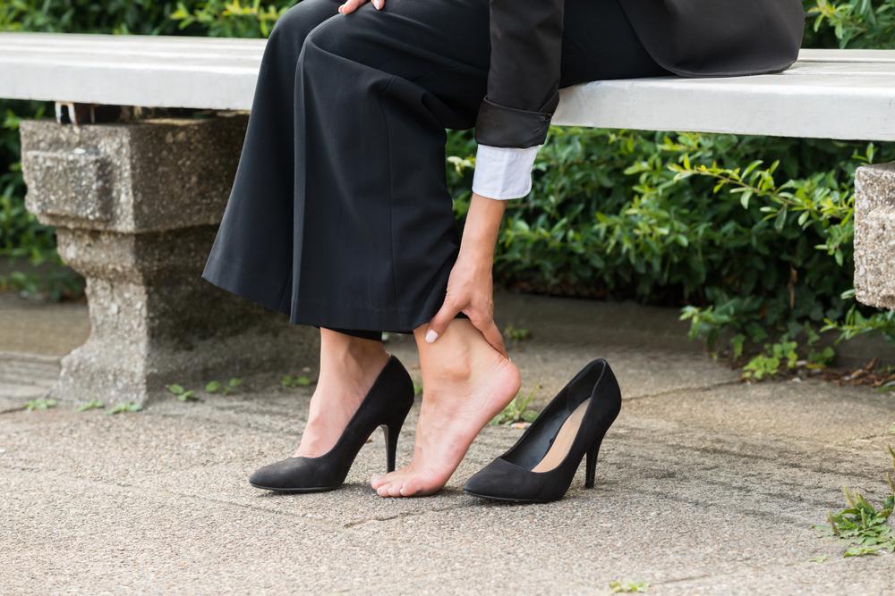 足が痛くなってパンプスを脱いでいる女性の足元