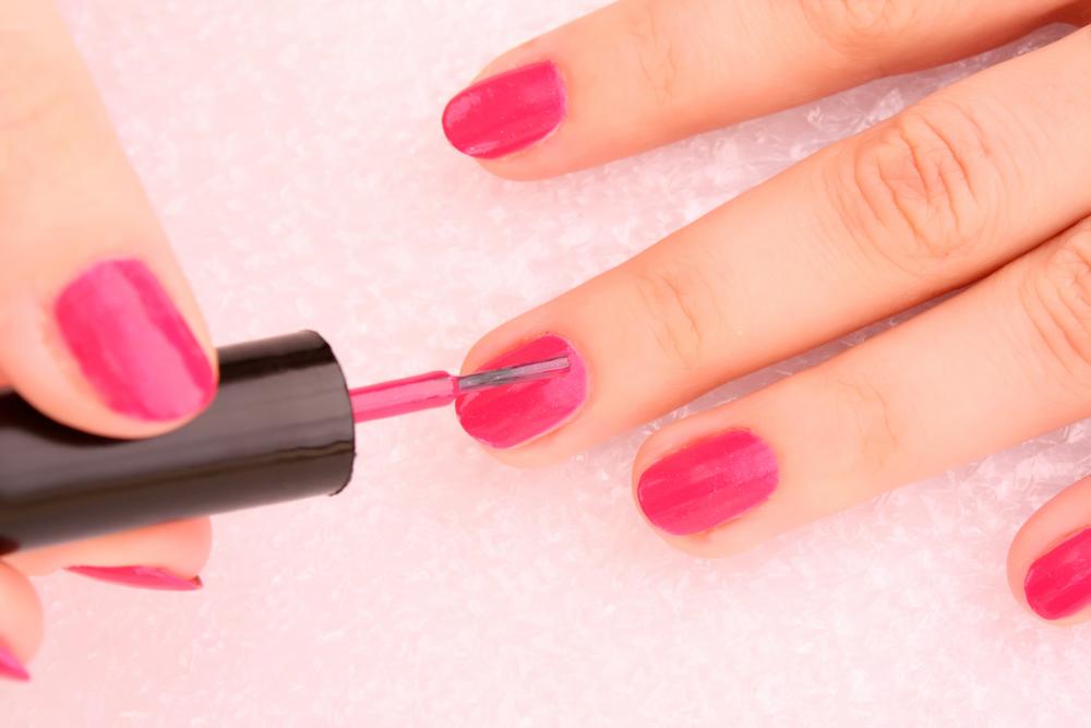 アイシャドウを塗る前に爪にベースカラーを塗っている女性