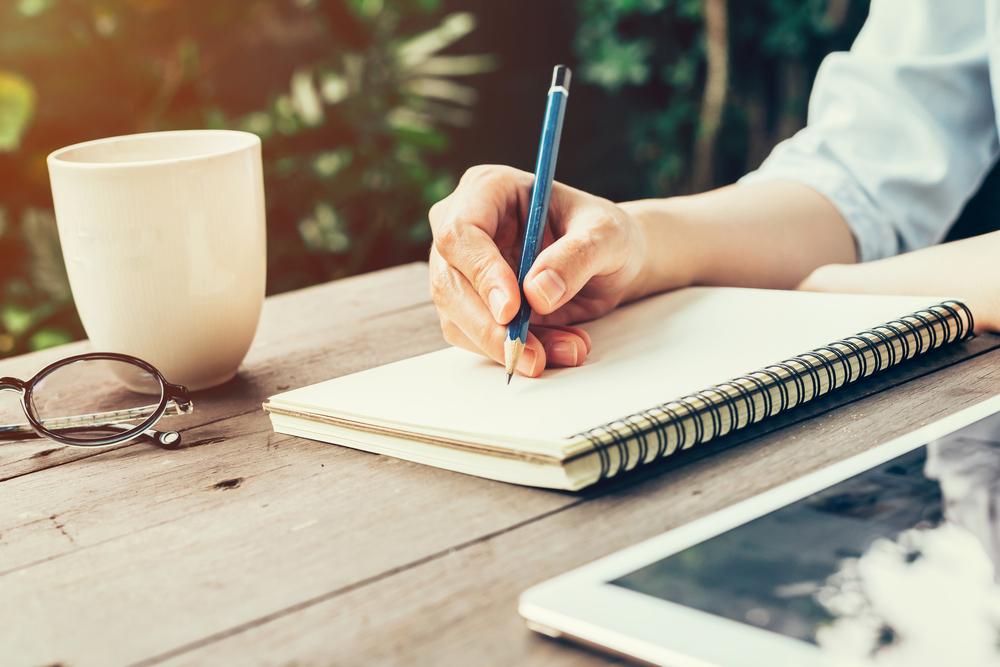 ノートとペンを持つ女性