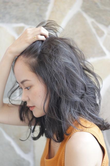 前髪をかき上げる女性