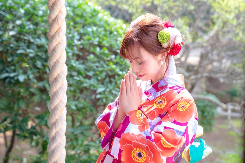 神社で拝む女性