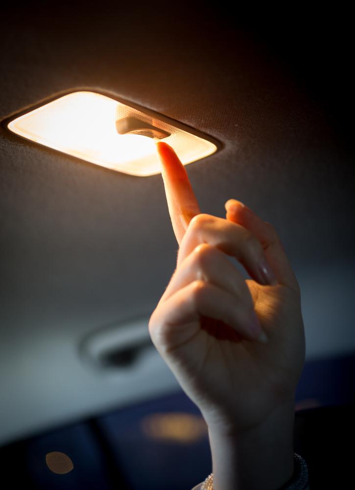夜行バスのライトをつける女性の手元