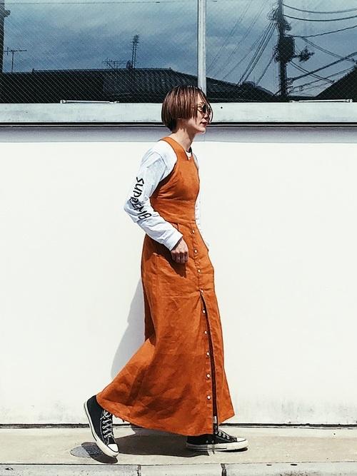 オレンジのマキシ丈ワンピ×白のスリーブロゴTシャツのコーデ