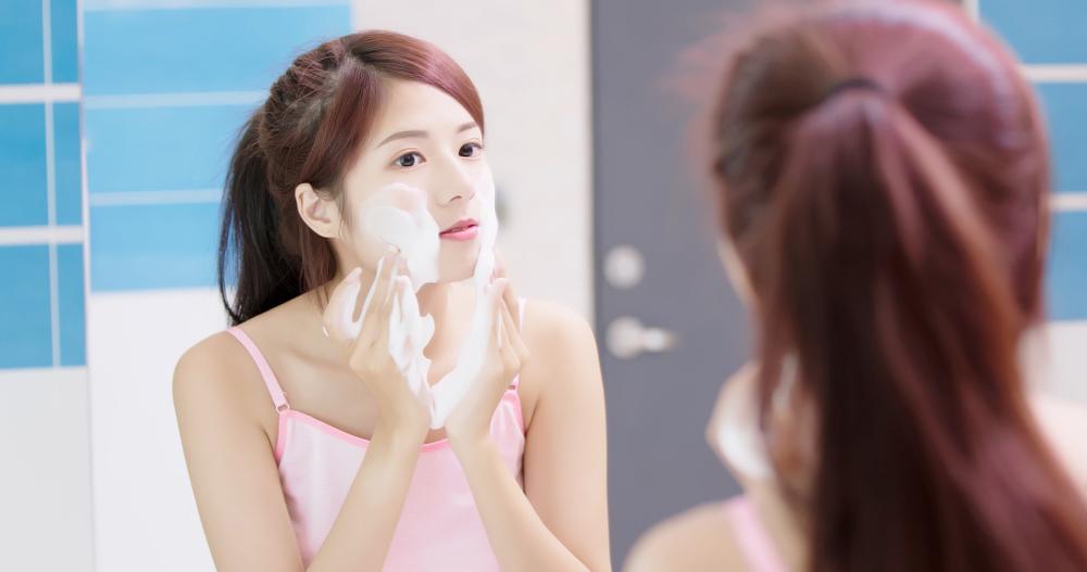 鏡を見ながら洗顔をしている人