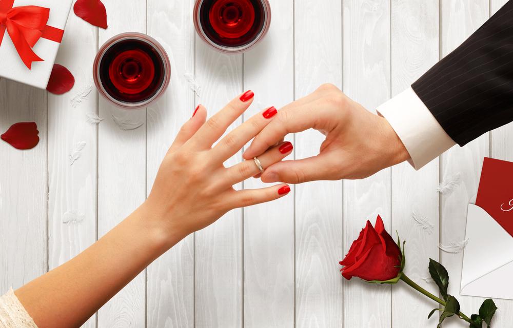 指輪をつけようとする男女の手