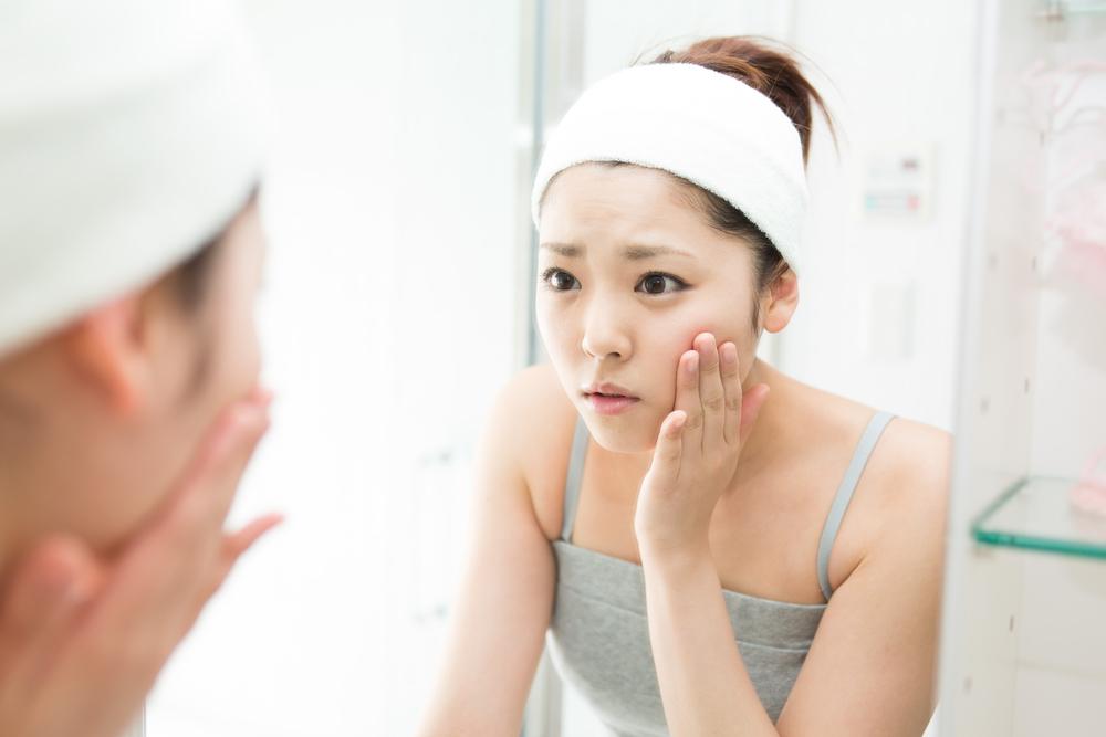 自分の肌を鏡で見ている女性