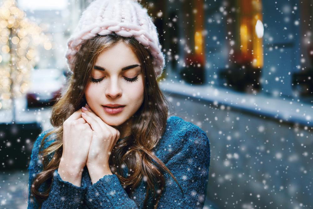 雪の中で目をつぶっている女性