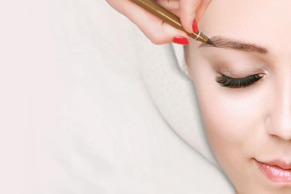 アイブロウペンシルで眉毛を描いている人