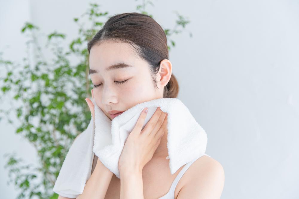 洗顔をしてタオルで顔をふく敏感肌の女性