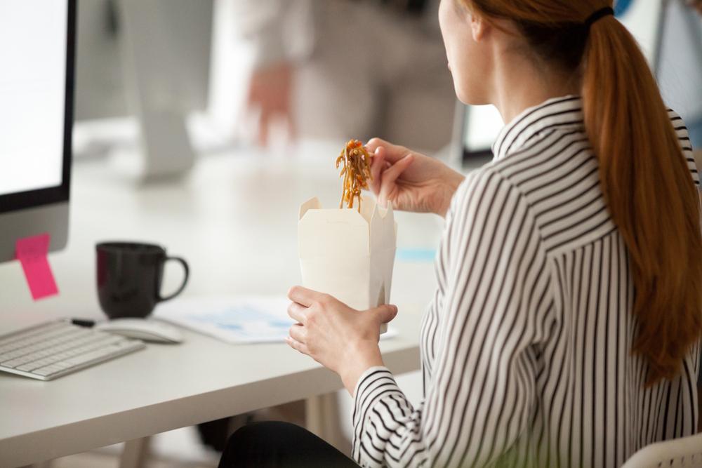 ジャンクフードを食べながら仕事をする女性
