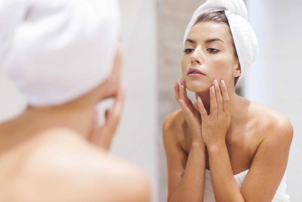 鏡でほうれい線をチェックする女性