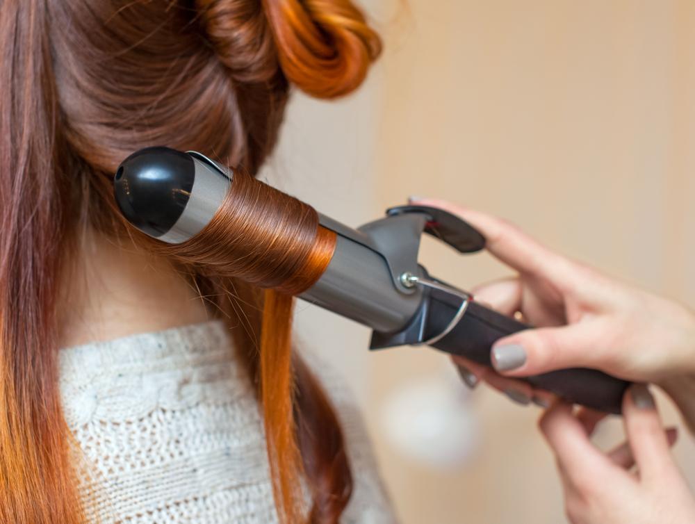 グラデーションヘアカラーの髪の毛をヘアアイロンでカールさせている女性