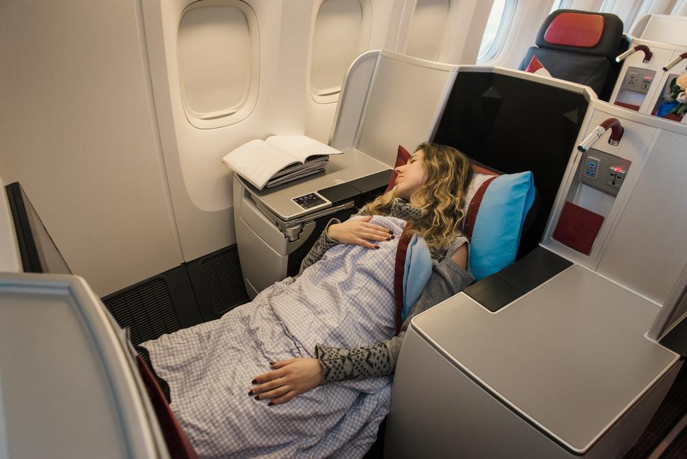 ビジネスクラスのシートで眠る女性