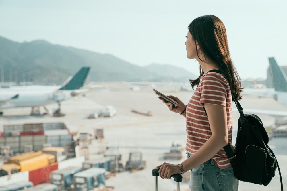 飛行場で搭乗を待つ女性