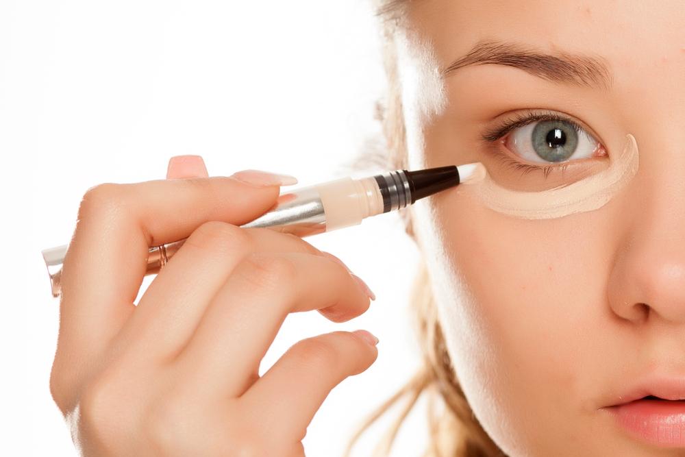 リキッドコンシーラーを目の下に塗る女性