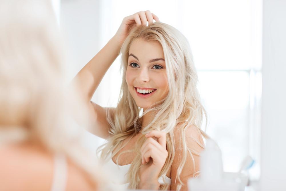 笑顔で鏡を見る女性