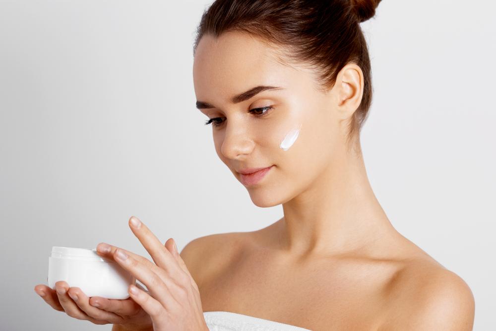 肌に基礎化粧品を塗る20代の女性