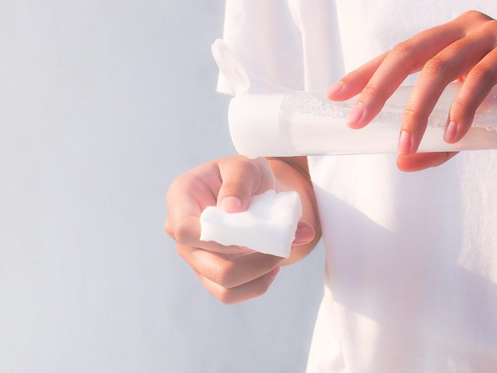 基礎化粧品の化粧水をコットンにとる女性