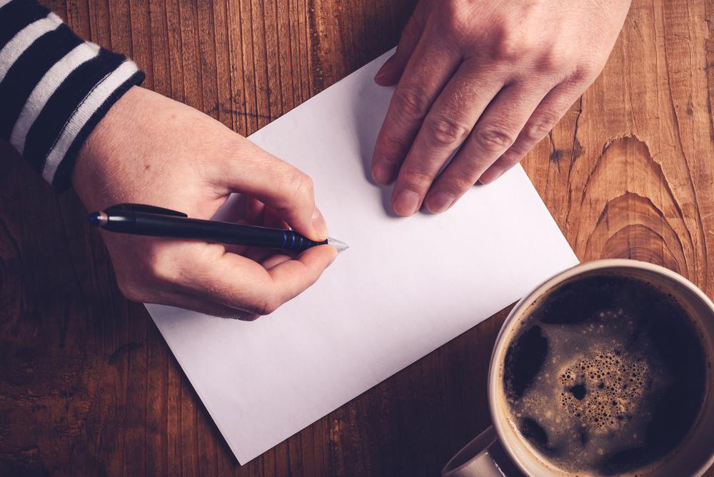 マナーを守ってはがきを書いている女性