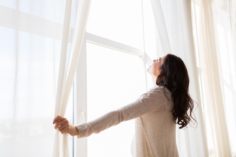 カーテンをあける女性