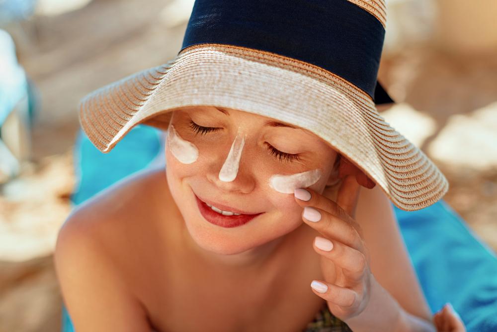 日焼け止めを鼻や頬に塗っている女性