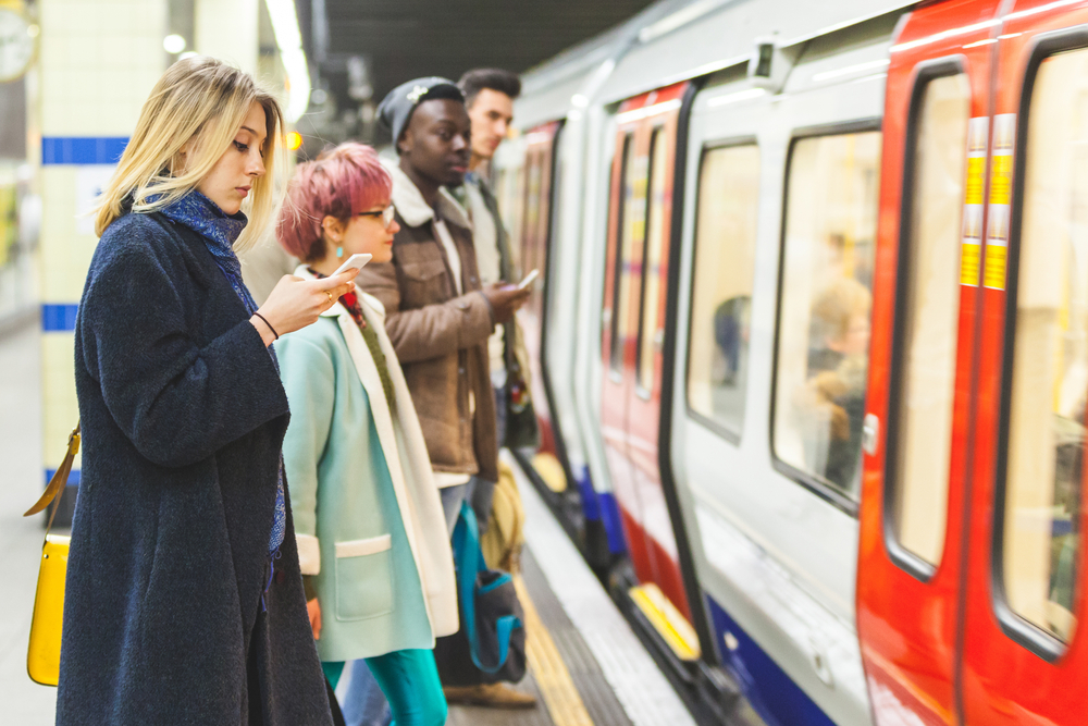 電車待ちでスマホを見ている女性