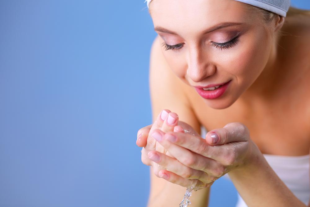 顔を水で流している女性
