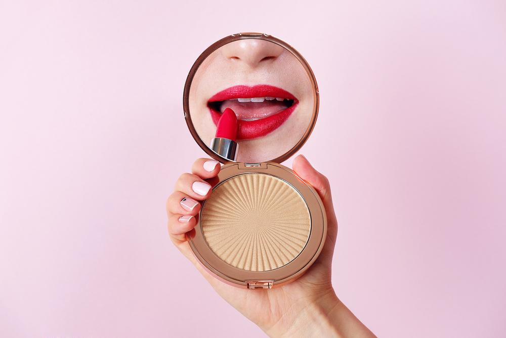 鏡を見ながら口紅を塗っている人