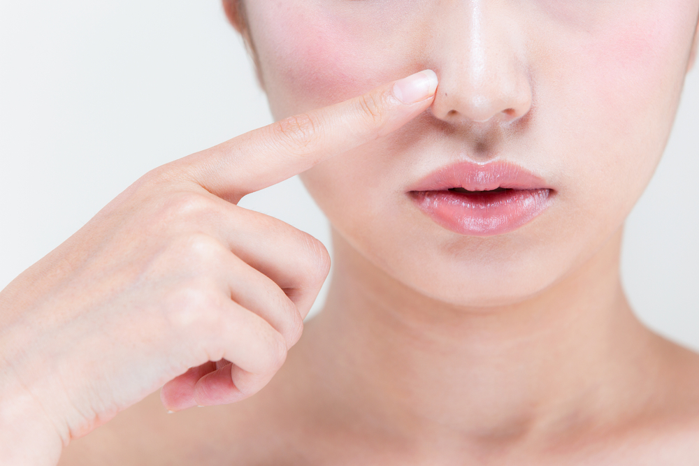 鼻を指す女性の写真