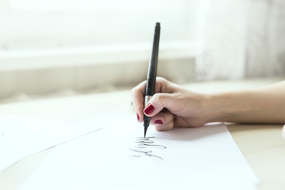 ペンで文字を書く女性の手