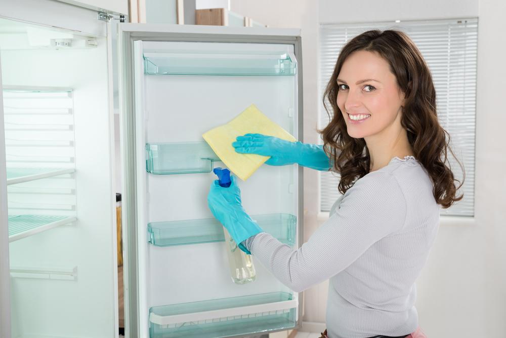 引っ越し前に冷蔵庫を掃除している女性