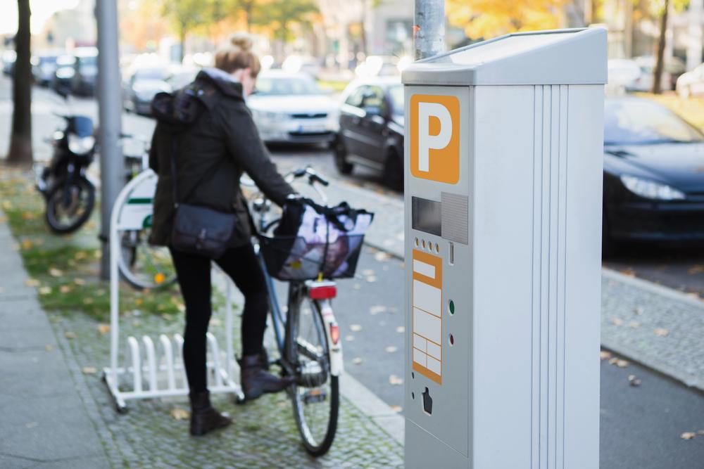 自転車を駐輪場に停めている女性