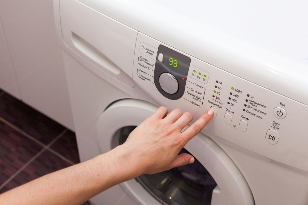 洗濯機を操作する女性の手元