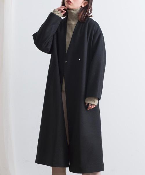 黒のノーカラーコートにタートルネックニットを合わせたコーデ