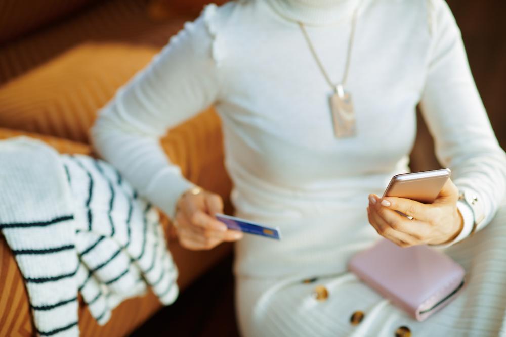 スマホとクレジットカードを持つ女性