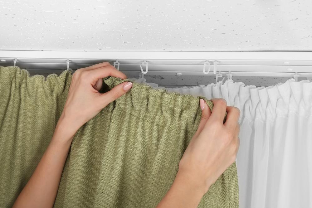カーテンをカーテンレールに掛ける女性の手元
