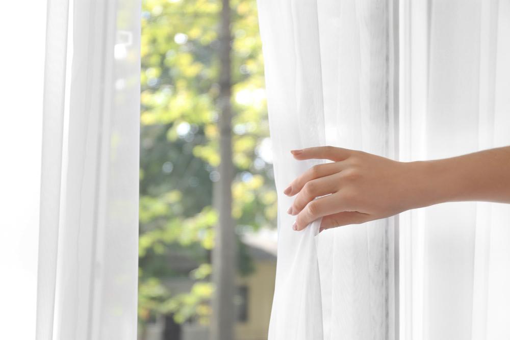 カーテンを開く女性の手元
