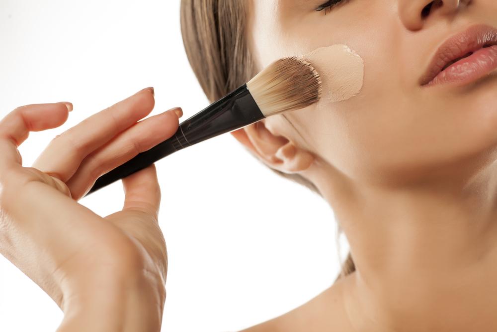 顔にファンデーションをブラシで塗る女性